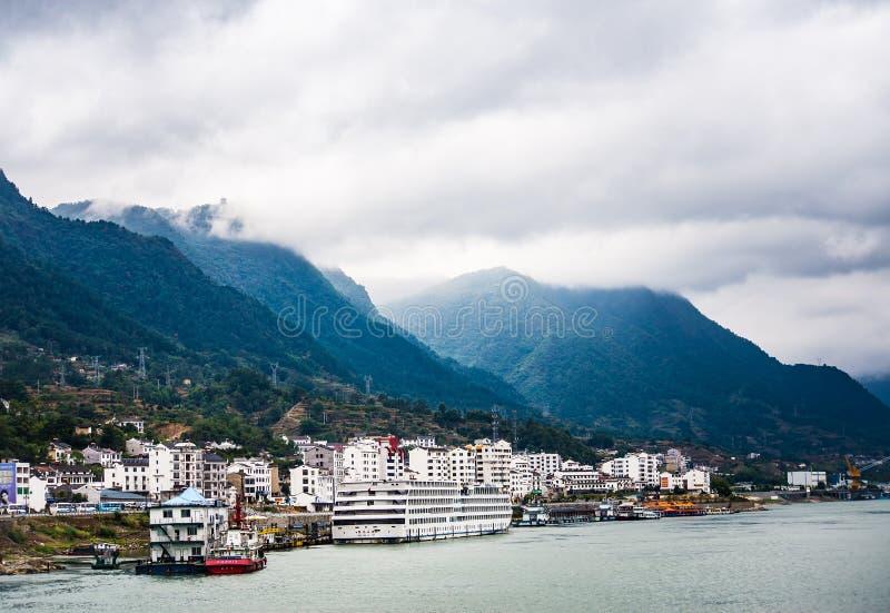 Kleine stad bij Yangtze-rivier` s rand met berg en wolkenachtergrond royalty-vrije stock afbeelding
