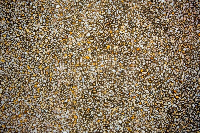 Kleine Steine auf Betonmauer, Kiesbeschaffenheitshintergrund Stapel der Kiesel lizenzfreie stockbilder