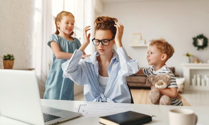 Kleine stoute kinderen leiden de druk bezette jonge vrouw af van het werk op een laptop thuis stock afbeelding