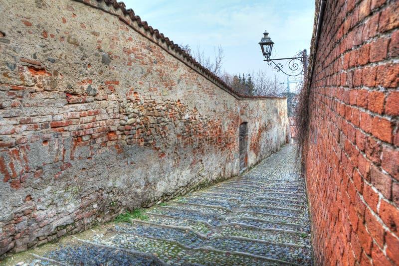 Kleine Straße unter alten Wänden in Saluzzo, Italien. stockbild
