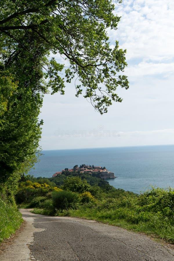 Kleine Straße zu Sveti Stefan mit Gras und Bäume im Weg Adriatisches Meer und Horizont Montenegro-Gebirgsstraße stockfoto
