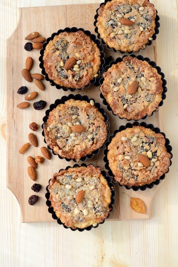 Kleine taartjes met noten en rozijnen die op een houten raad vullen stock afbeelding