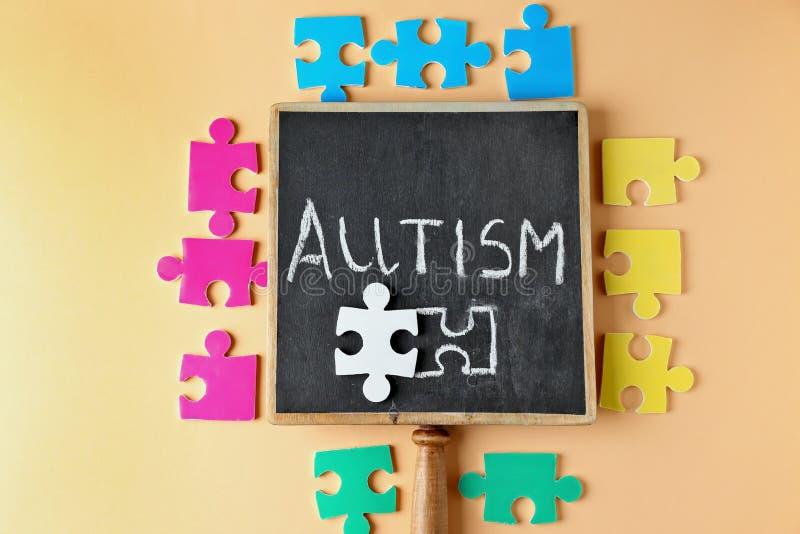 Kleine Tafel mit Wort AUTISMUS und Puzzlespiele lizenzfreies stockfoto
