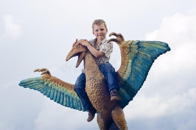 Kleine tapfere Kinder auf einem Dinosaurier in einem Park stockfoto