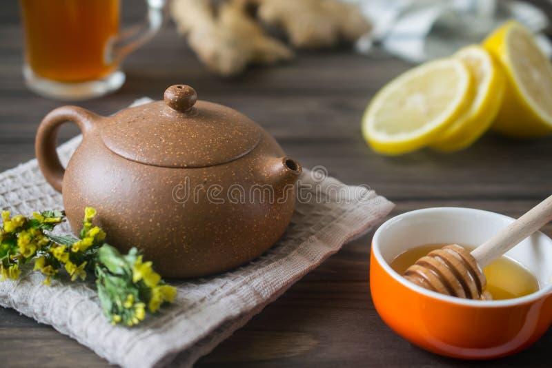 Kleine Teekanne mit Kräutertee auf Holztisch mit Zitrone und Honig stockfoto