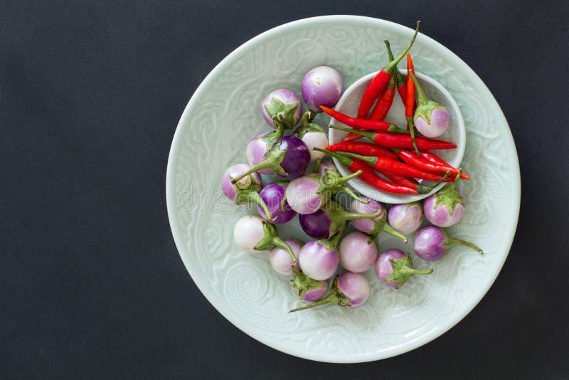 Kleine thailändische Auberginen und glühende Paprikapfeffer auf grüne Platten auf einem schwarzen Hintergrund Draufsicht, asiatis lizenzfreie stockfotos