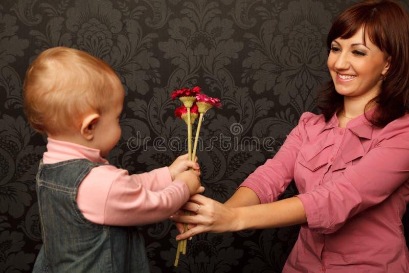 Kleine Tochter gibt ihr Mutterblumen lizenzfreie stockfotos