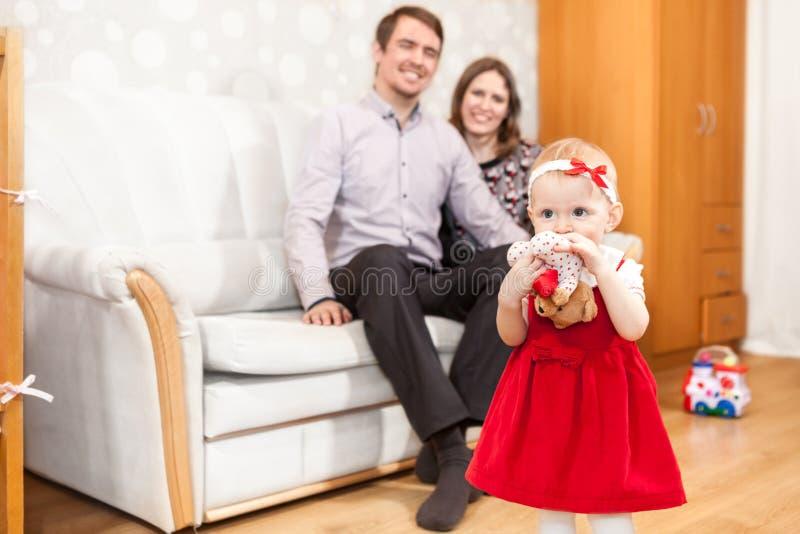 Kleine Tochter mit dem Sitzen auf Sofavater und -mutter stockfoto