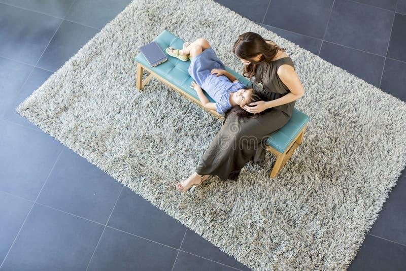 Kleine Tochterlage auf ihrem Mutter ` s Schoss und genießen, sehen vom Abo an lizenzfreie stockbilder