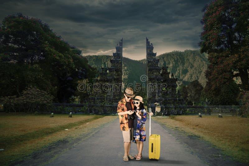 Kleine toerist twee die een telefoon op de weg met behulp van royalty-vrije stock afbeelding