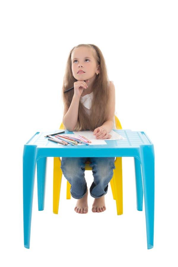 Kleine träumende Mädchenzeichnung unter Verwendung der Farbbleistifte an lokalisiert lizenzfreies stockbild