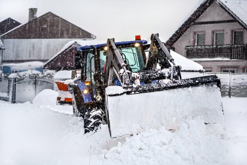 Kleine tractor met ploeg die sneeuwladingen tijdens zware sneeuwstormramp, dorpshuizen op achtergrond verwijderen stock afbeelding