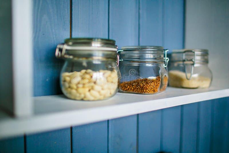 Kleine transparante kruiken voor voedsel op houten plank royalty-vrije stock afbeeldingen