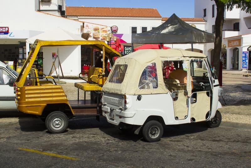 Kleine Tuk Tuks parkeerde terwijl het wachten op een vervoerprijs bij de bovenkant van de strook in Albuferia in Portugal royalty-vrije stock fotografie
