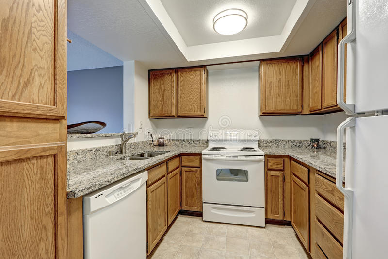 Kleine u vormige die keuken met houten kabinetten wordt gevuld stock