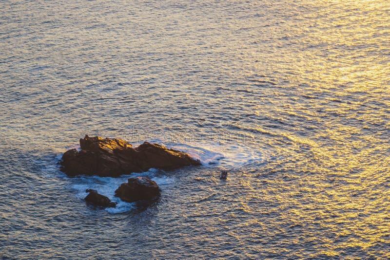 Kleine uiterst kleine boot met het breken van golven dicht bij een klein rotseiland bij zonsondergang, Kaap Roca stock fotografie
