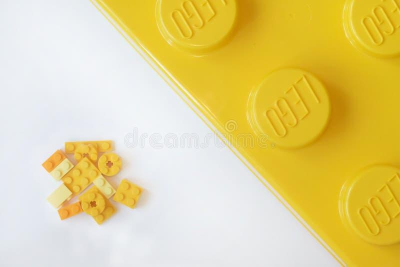 Kleine und große gelbe lego Ziegelsteine auf weißem Hintergrund Populäre Spielwaren stockbild