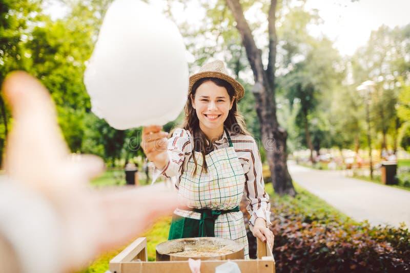 Kleine van het bedrijfs fotothema kokende snoepjes Een jonge Kaukasische vrouw met een schorthandelaar in de hoed de eigenaar van stock fotografie