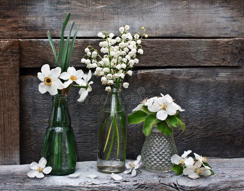 Kleine vazen en flessen met de lentebloemen royalty-vrije stock fotografie