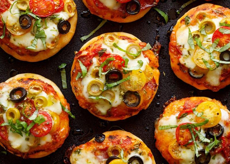 Kleine vegetarische Pizzas mit den verschiedenen Arten des Zusatzes des Gemüses, des Mozzarellakäses und des frischen Basilikums lizenzfreie stockfotos
