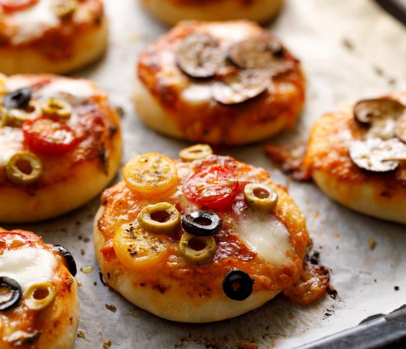 Kleine vegetarische Pizzas mit den verschiedenen Arten des Zusatzes des Gemüses und des Mozzarellakäses und des frischen Basiliku stockfotos