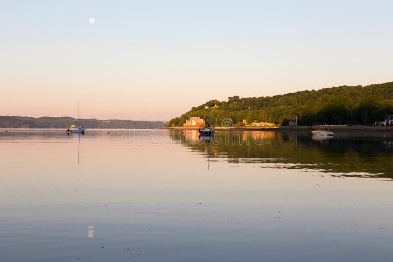 Kleine verankerde zeilboten en motorboot in St Lawrence River tijdens een mooie de vroege zomerochtend stock afbeeldingen