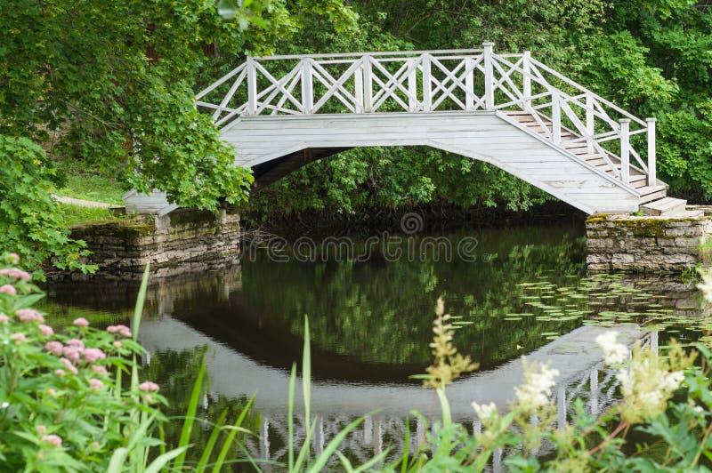 Kleine vijver en decoratieve witte houten brug stock fotografie