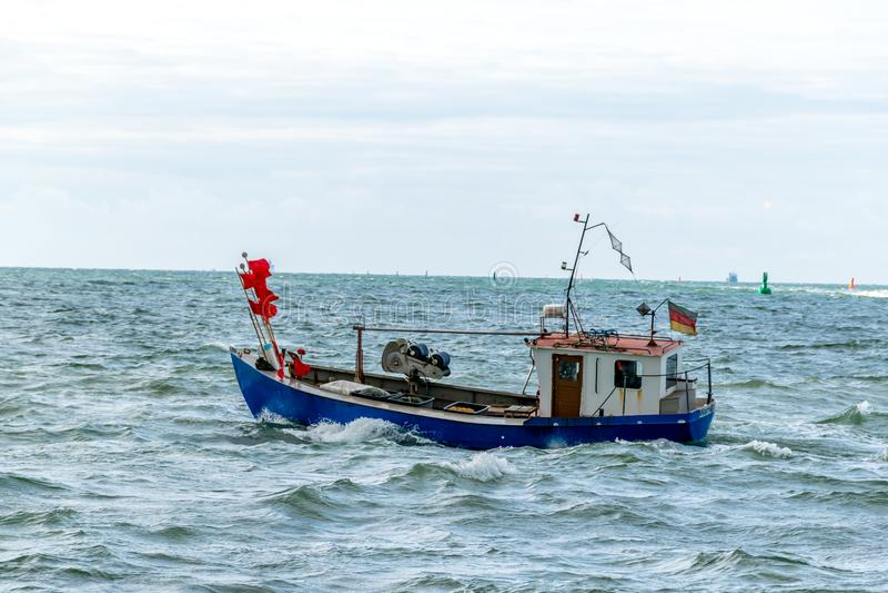 Kleine vissersboot op het water met lichte overzeese storing stock fotografie