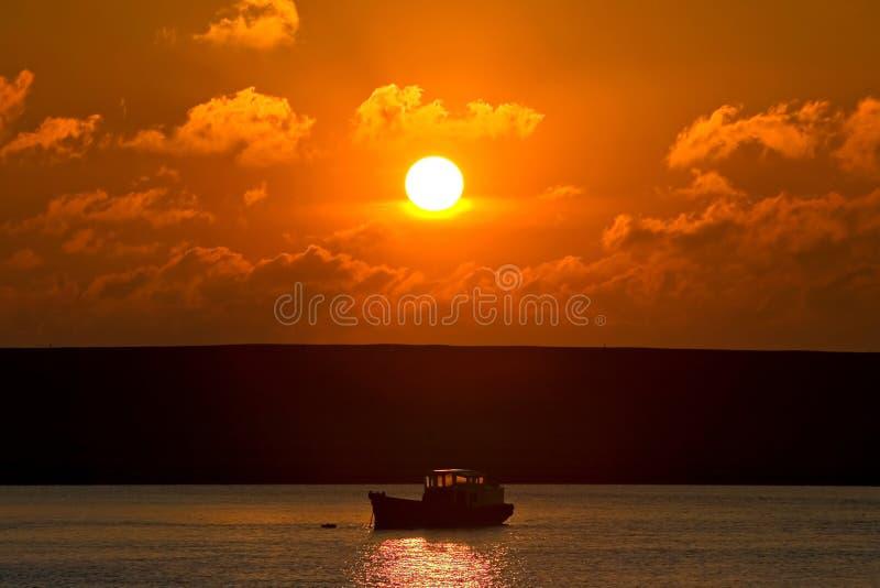 Kleine vissersboot op zijn uitweg aan overzees bij zonsondergang royalty-vrije stock foto's