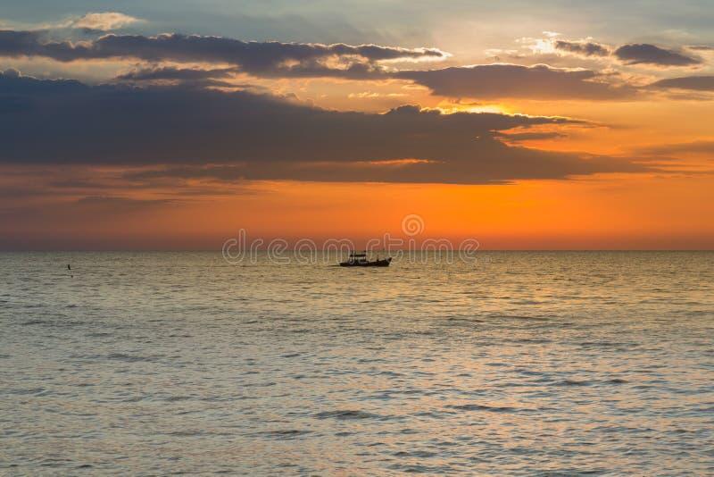 Kleine vissersboot over zeekusthorizon en na zonsondergang stock afbeeldingen