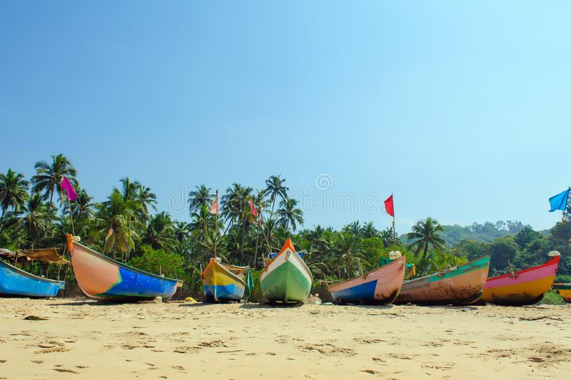Kleine vissersboten in reggaekleuren op oceaanstrandkust tegen blauwe hemel India, Goa, Maharashtra stock afbeelding