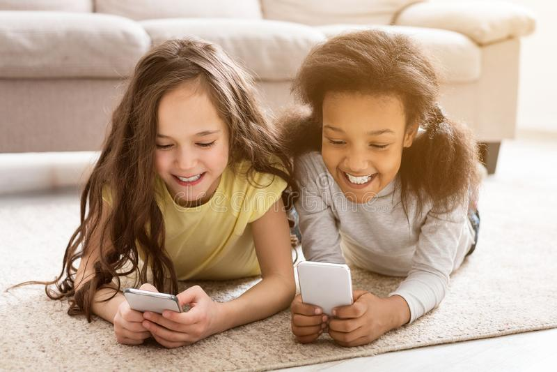 Kleine vrienden die op smartphones spelen, die op vloer liggen royalty-vrije stock afbeelding