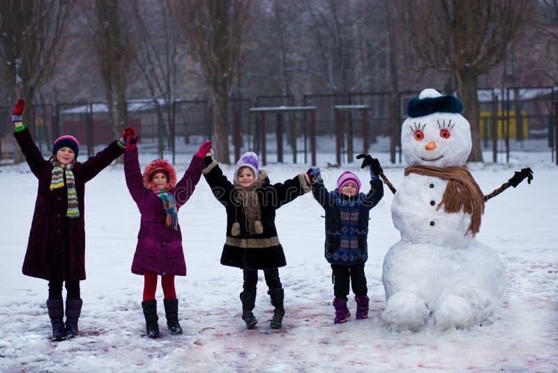 Kleine vrolijke meisjes dichtbij grote grappige sneeuwman stock foto