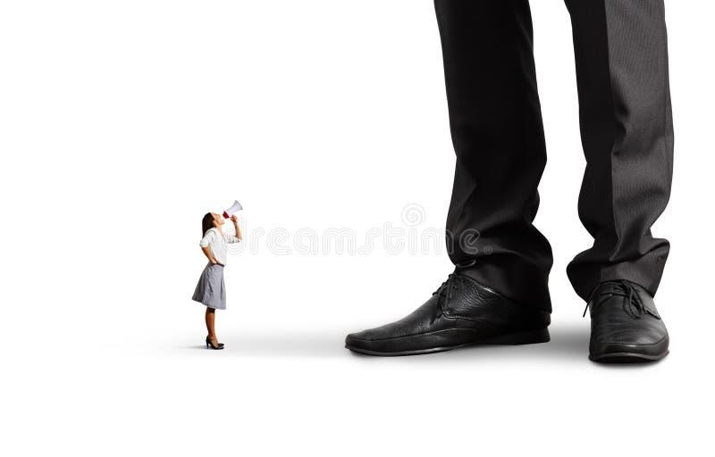 Kleine vrouw die bij grote werkgever gillen stock foto's
