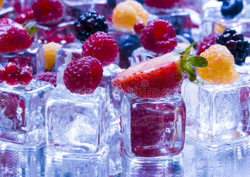 Kleine vruchten onder ijsblokjes stock fotografie