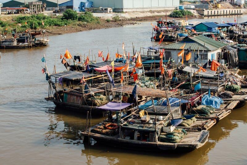 Kleine vuile rivier met boten en bruggen in Azië stock foto