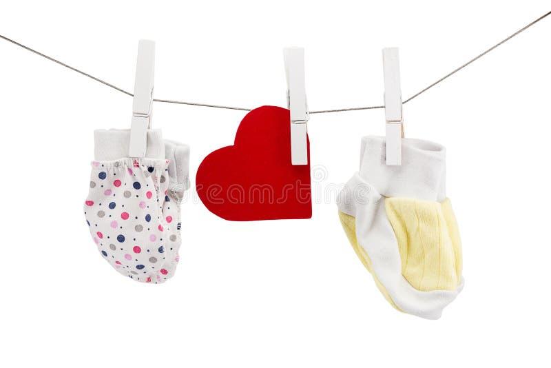 Kleine vuisthandschoenen en sokken voor pasgeborenen stock foto