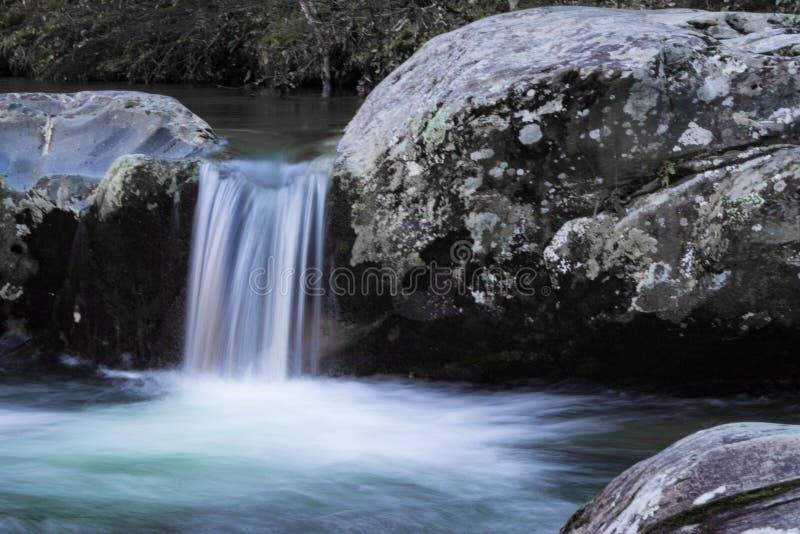 Kleine Wasserfallkaskade zwischen zwei großen Felsen lizenzfreies stockbild