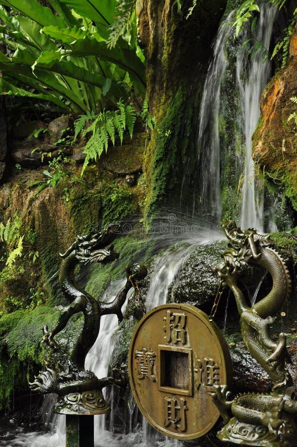 Kleine waterval en traditionele Chinese tempelstandbeelden royalty-vrije stock fotografie