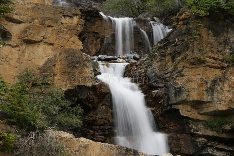 Kleine waterval in rotsachtig stock afbeelding