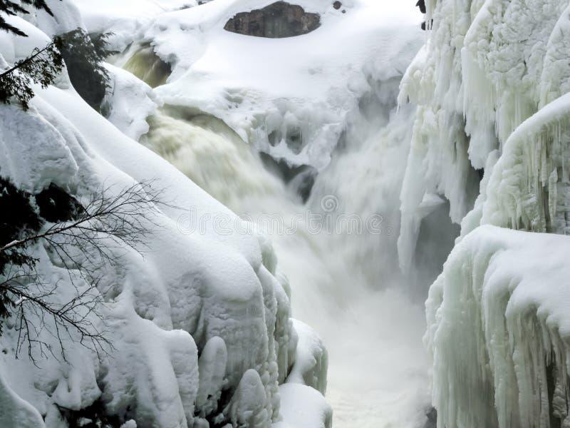 Kleine watervallen die in smalle rivier met banken omvat in sneeuw en ijskegel draperen stock foto