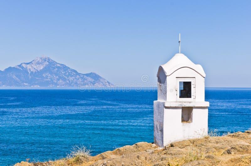 Kleine weiße Kirche oder Kapelle mit dem heiligen Athos im Hintergrund lizenzfreie stockfotografie