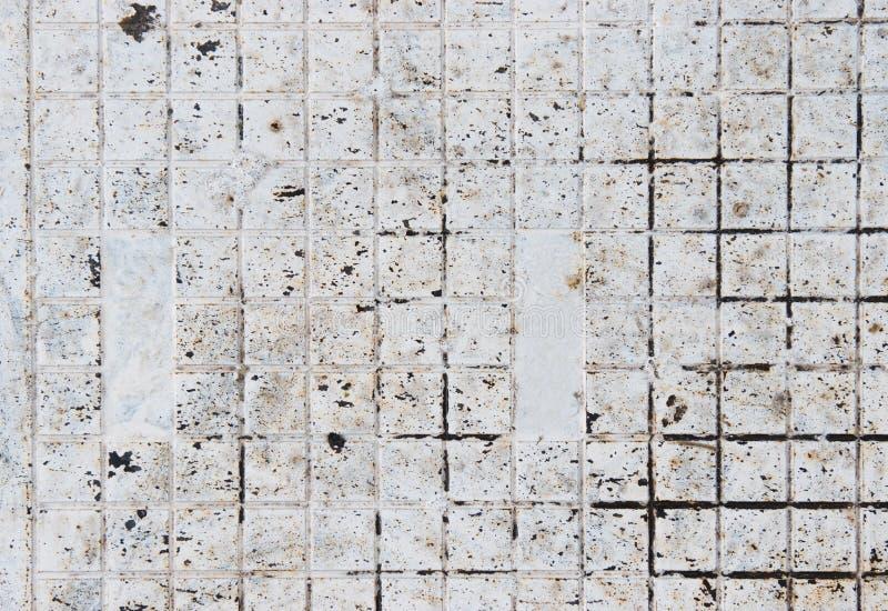 Kleine Weißmetallquadratfliesen bedeckt mit Schmutz Weißer Hintergrund gemacht aus kleinen Fliesen heraus stockbild