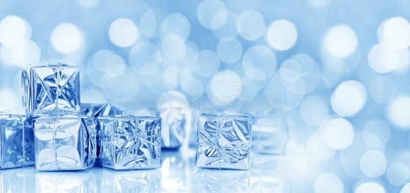 Kleine Weihnachtsgeschenke im glänzenden Papier, panoramischer blauer Hintergrund stockfoto