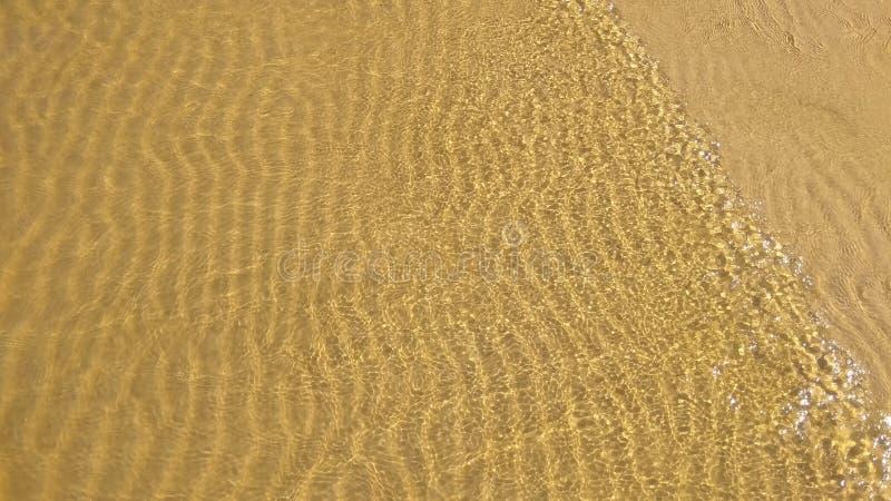 kleine Wellen des sandigen Wassers der Küstenleichten brise transparenten klaren bilden ein Muster auf dem Sand stockbilder