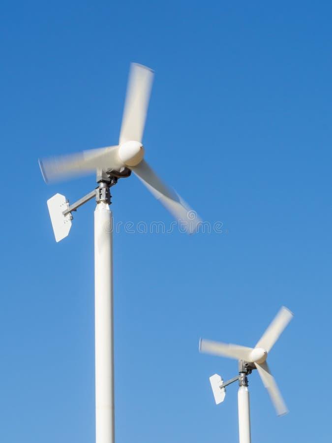 Kleine windturbines met duidelijke blauwe hemel (motieonduidelijk beeld) stock afbeeldingen