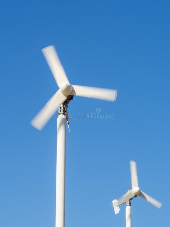 Kleine windturbines met duidelijke blauwe hemel (motieonduidelijk beeld) stock fotografie