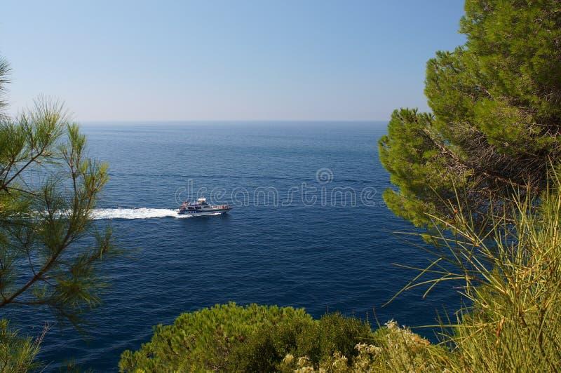 Kleine witte boot die in blauwe overzees met toeristen drijven royalty-vrije stock afbeeldingen