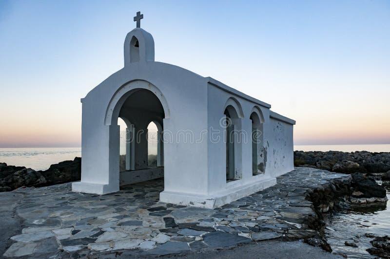 Kleine witte kerk naast overzees stock afbeeldingen