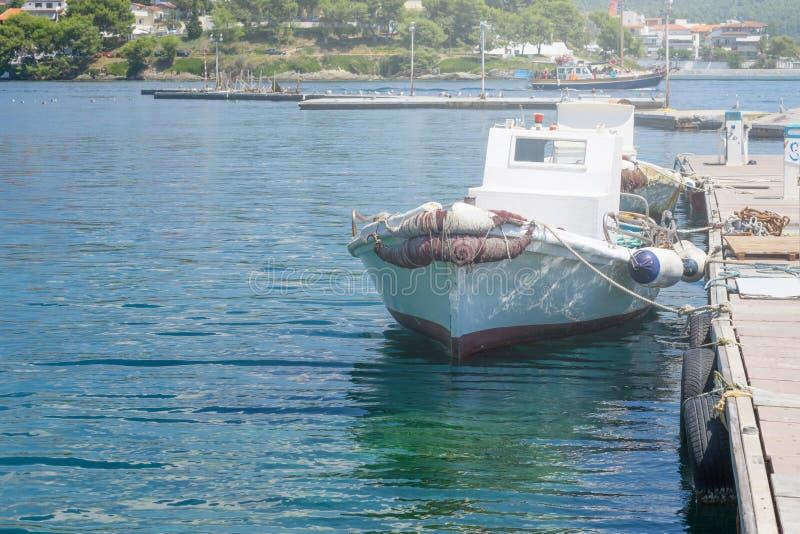 Kleine witte vissersboot die naast het dok in stad wordt verankerd royalty-vrije stock afbeelding